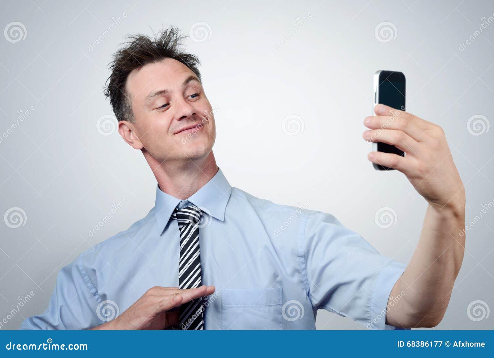 Lustiger Geschäftsmann, der auf einem Smartphone sich fotografiert