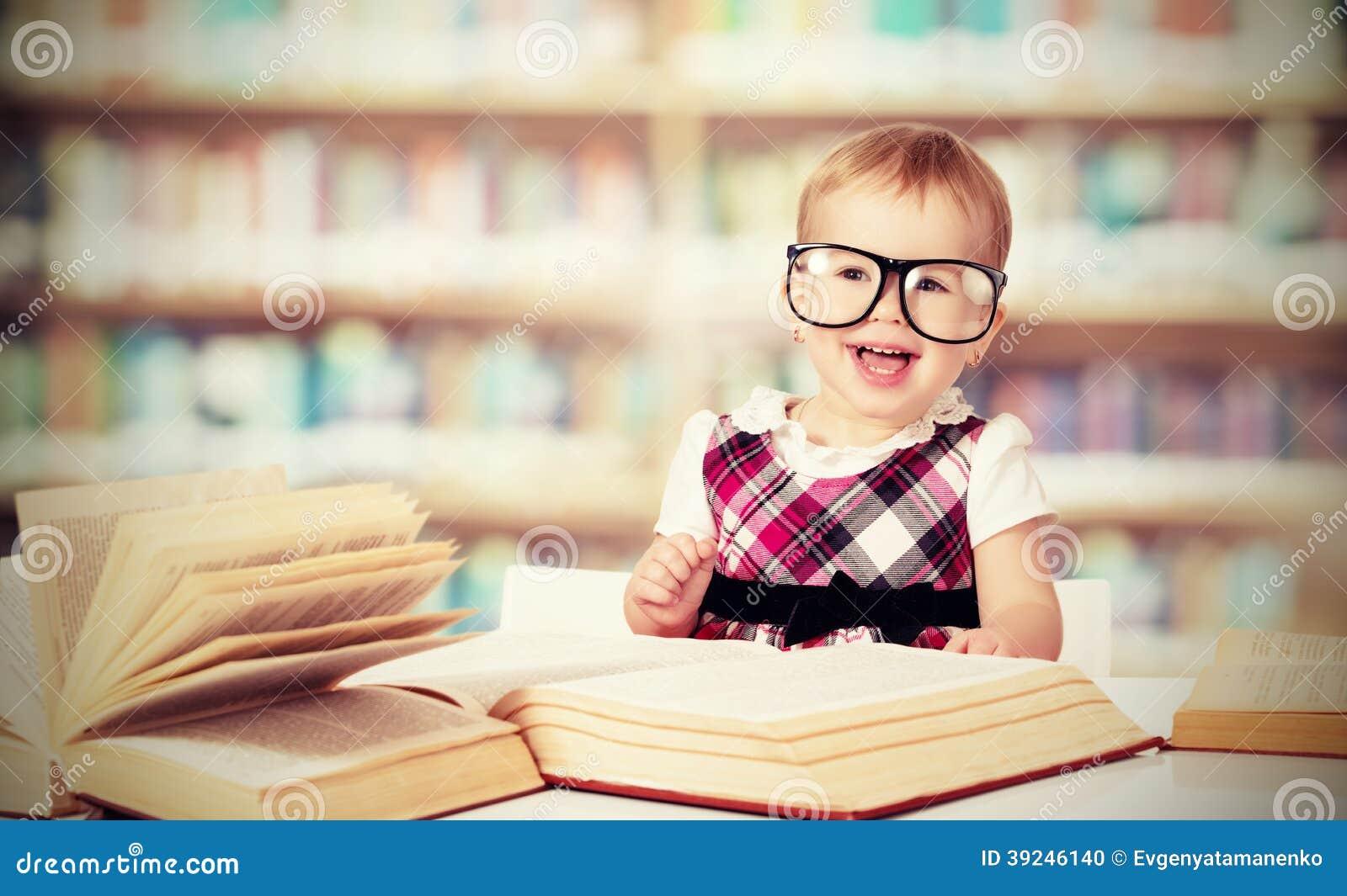 Lustiges Baby im Glaslesebuch in der Bibliothek