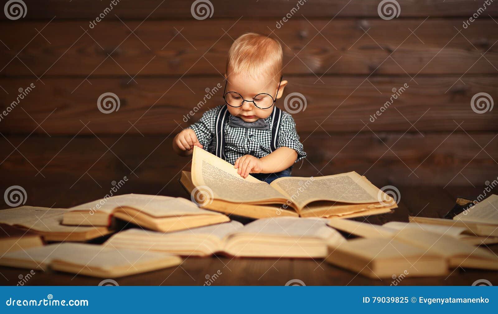 Lustiges Baby mit Büchern in den Gläsern