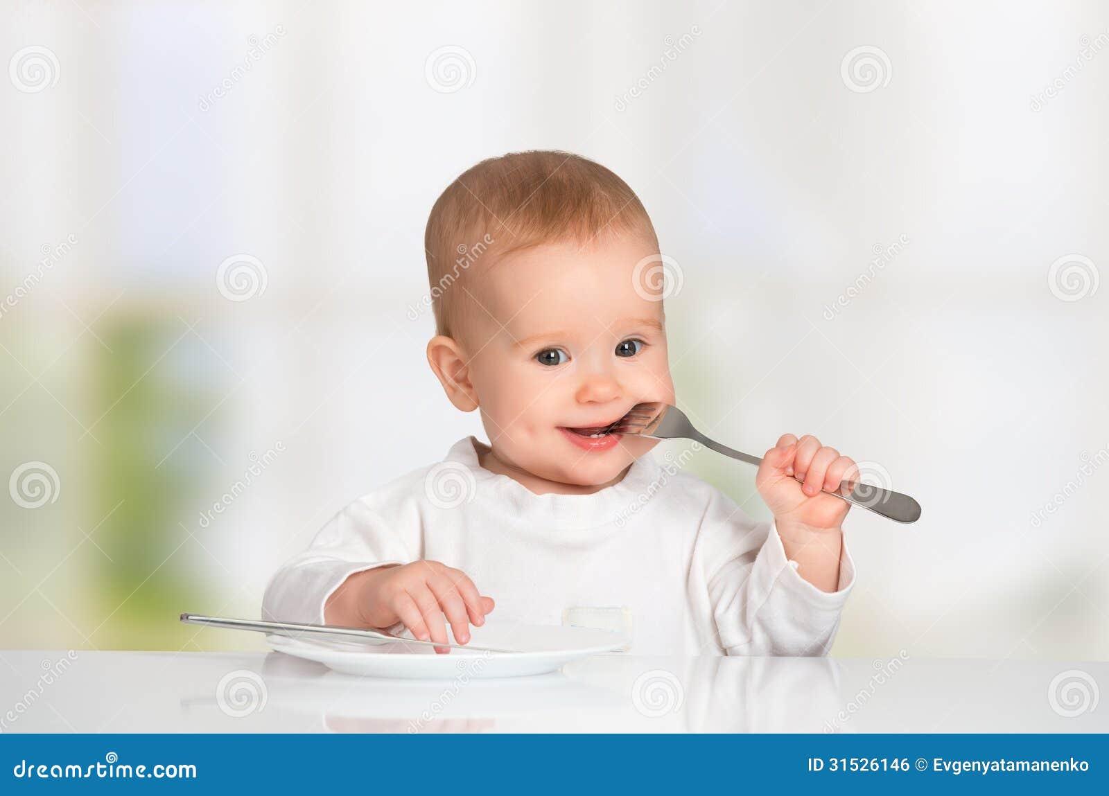Lustiges Baby mit einem Messer und einer Gabel Lebensmittel essend
