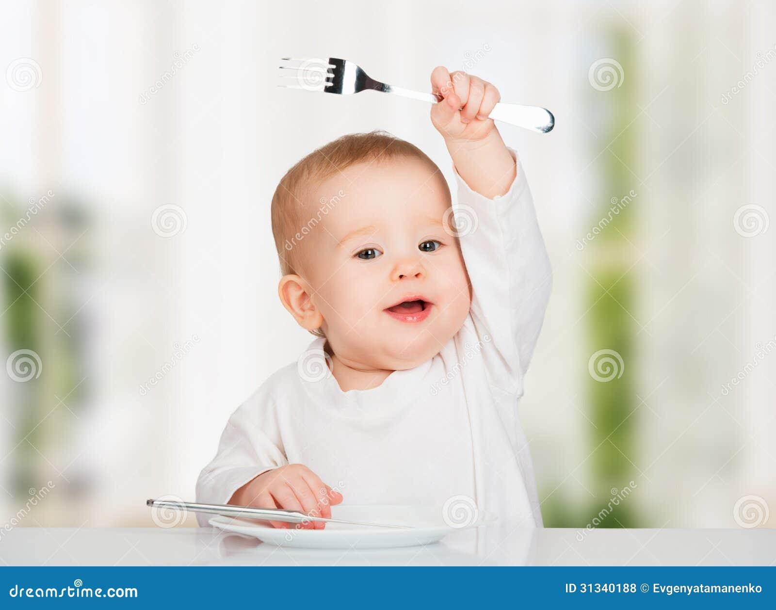 Lustiges Baby mit einem Messer und einer Gabel Nahrung essend