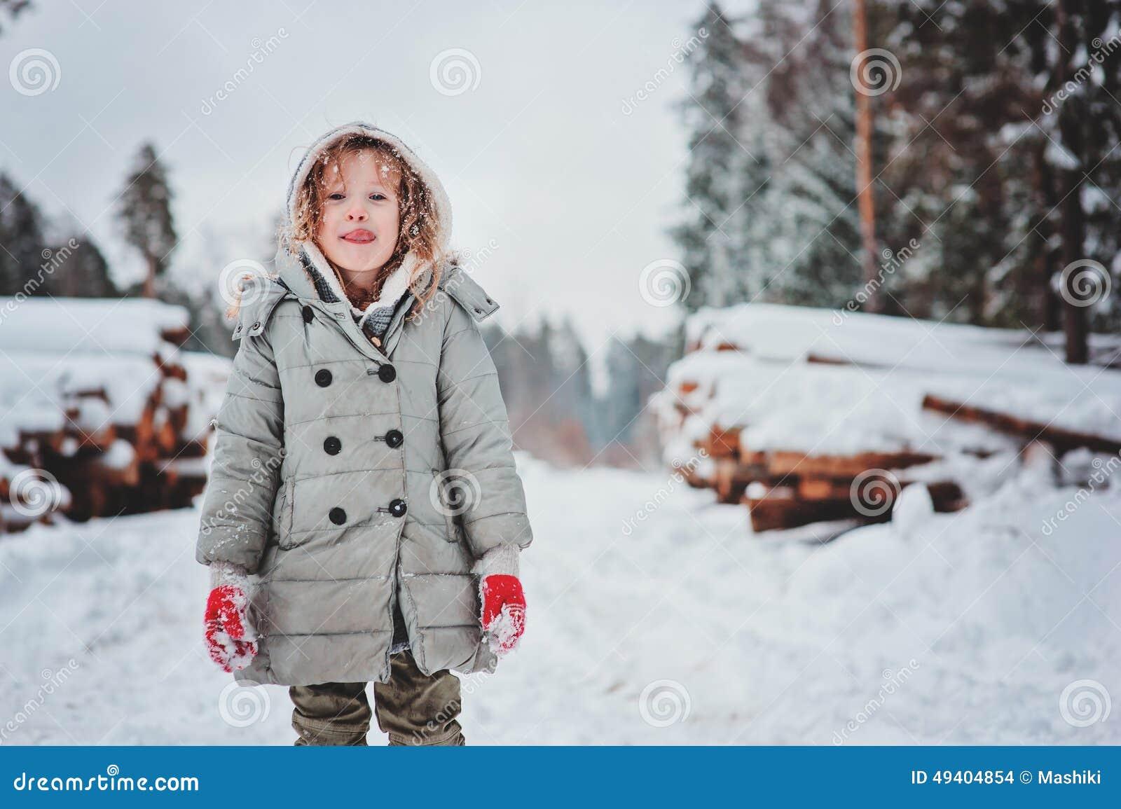 Download Lustiges Glückliches Kindermädchenporträt Auf Dem Weg Im Schneebedeckten Wald Des Winters Mit Baumholzschlag Auf Hintergrund Stockfoto - Bild von handschuhe, zicklein: 49404854