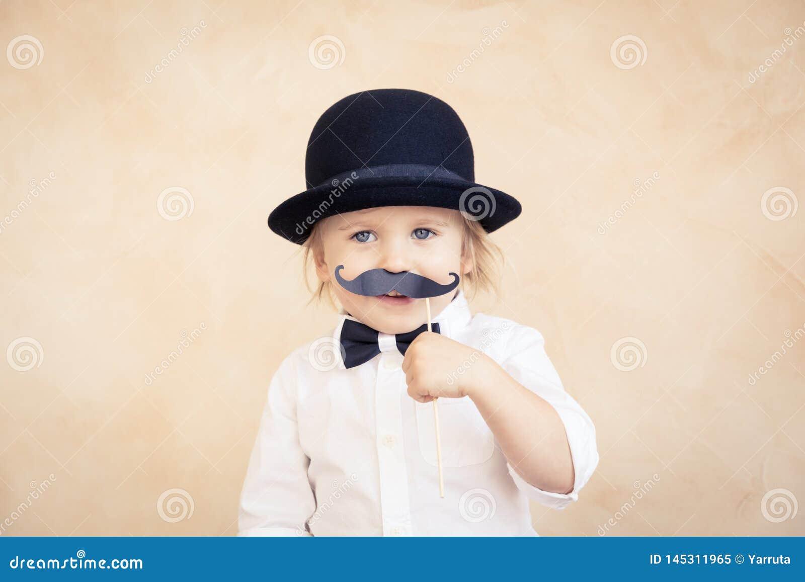 Lustiges Kind mit dem gef?lschten Papierschnurrbart