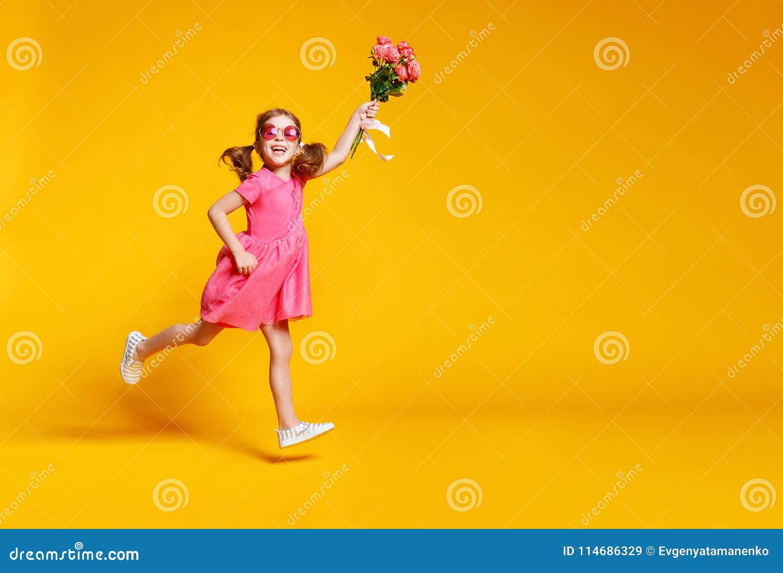 Lustiges Kindermädchen läuft und springt mit Blumenstrauß von Blumen auf Farbe