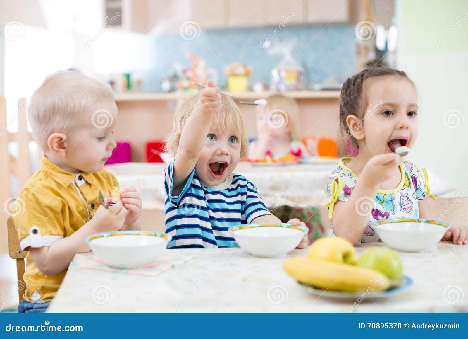 Lustiges Kleinkind, das im Kindergarten spielt und isst