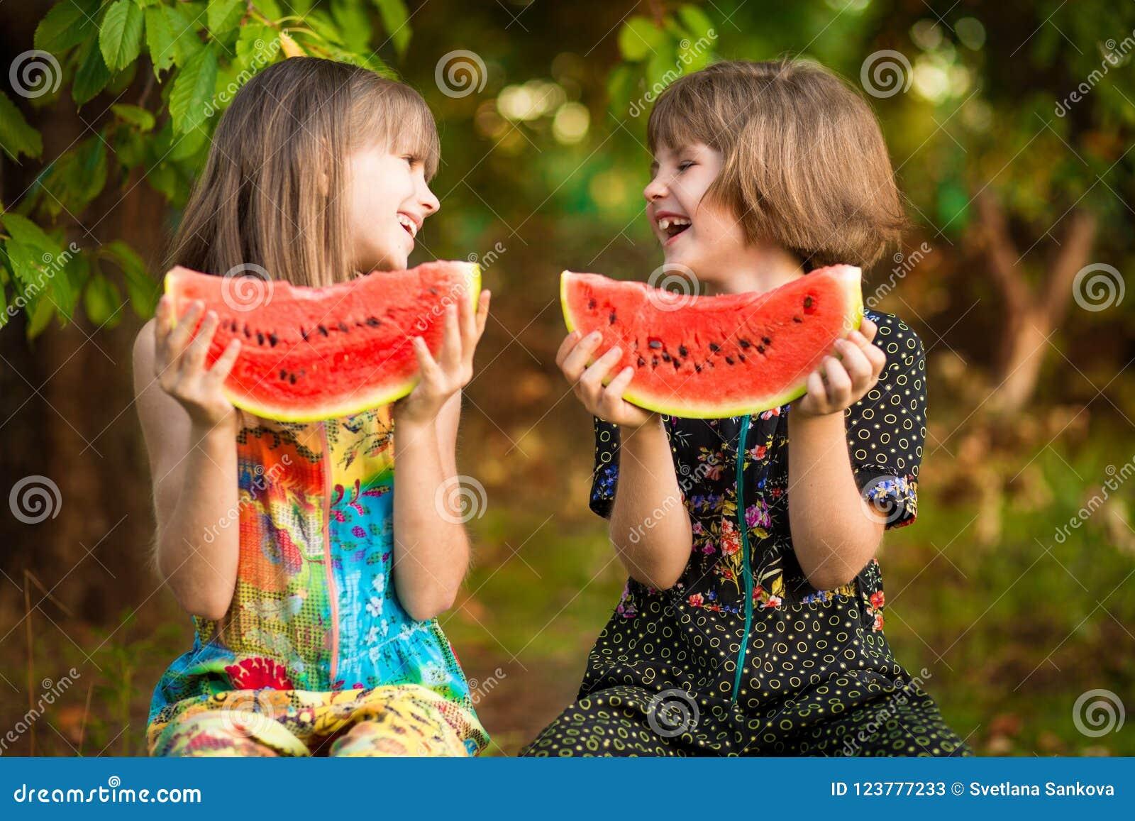 Lustiges Mädchen der kleinen Schwestern isst Wassermelone im Sommer