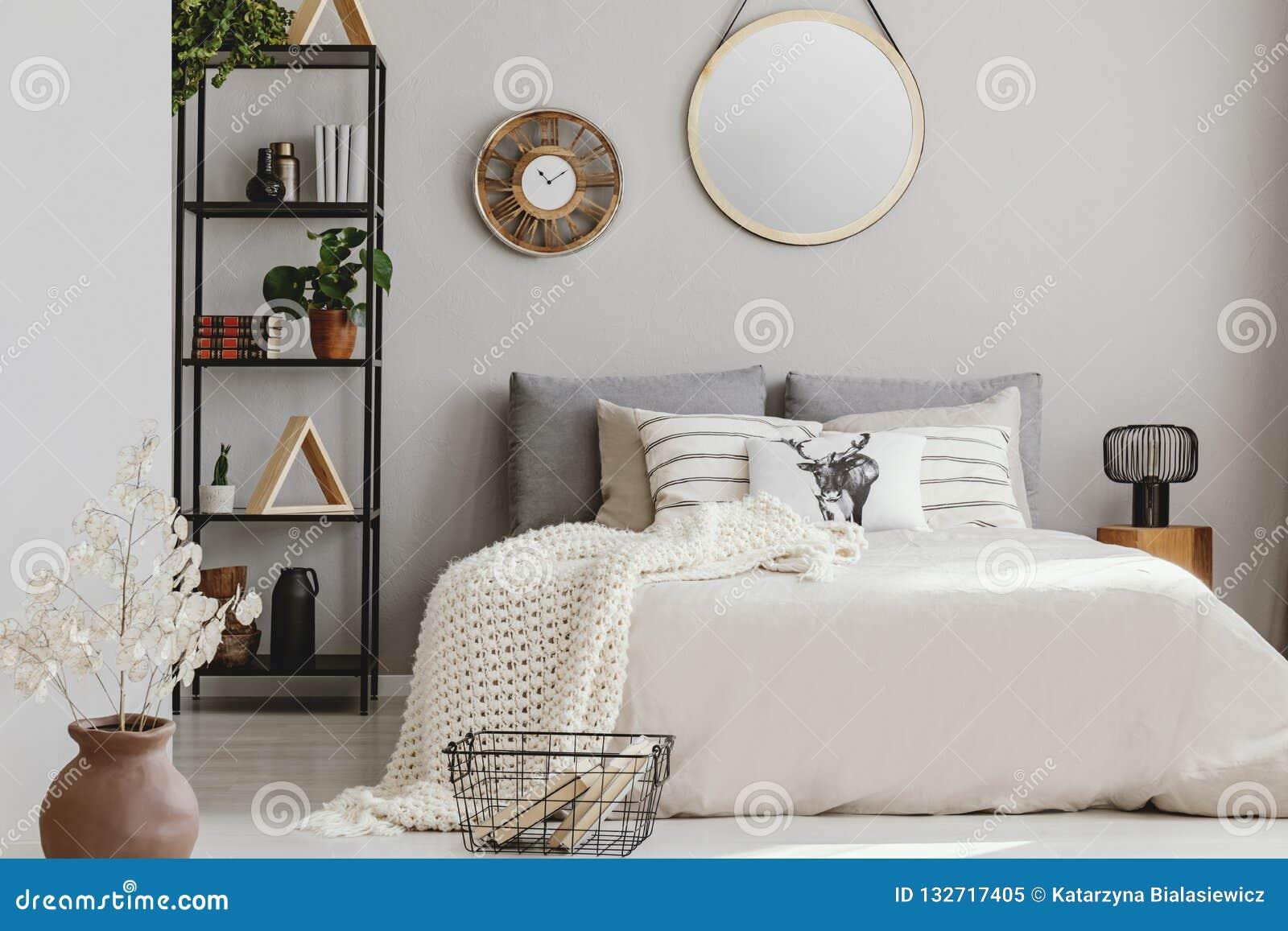 Lustro i drewniany zegar na ścianie elegancka sypialnia z beżową ciepłą koc pościeli i bielu, istna fotografia