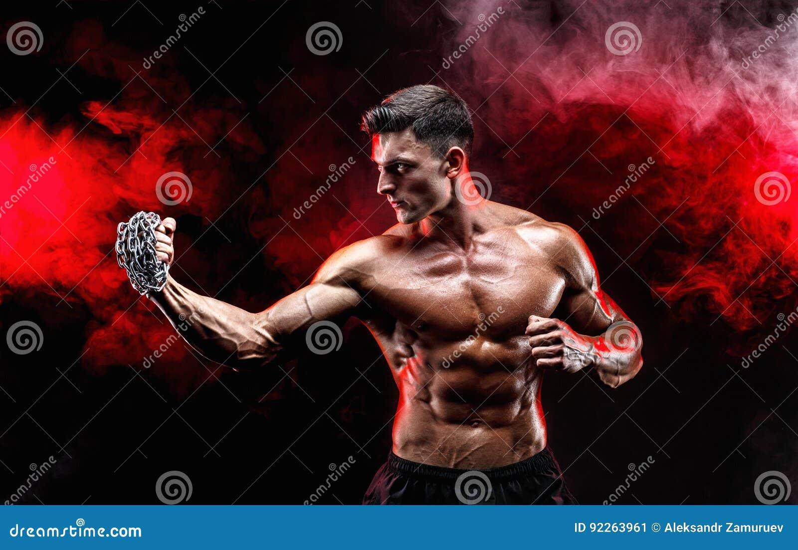 Lutador muscular sério que faz o perfurador com as correntes trançadas sobre seu punho