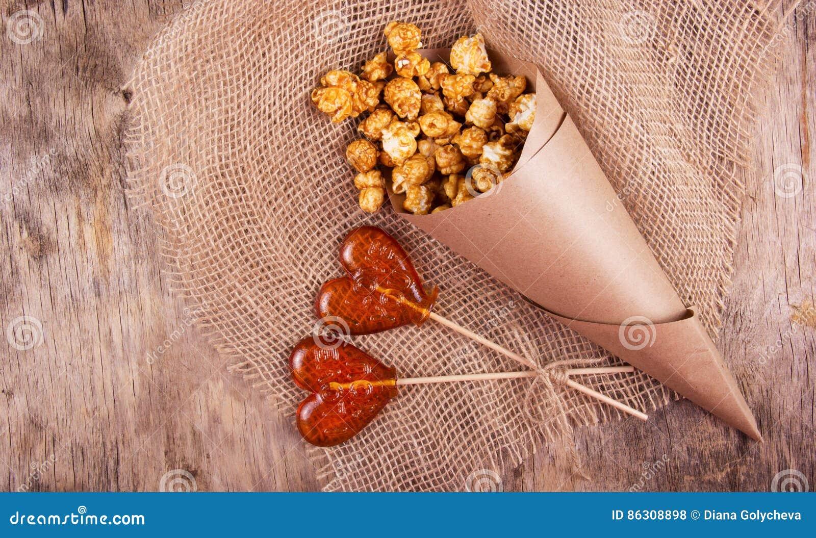 Lutscher zwei in Form eines Herzens und eine Papiertüte Karamellpopcorn auf hölzernem Hintergrund