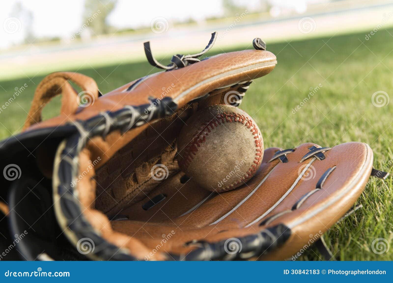 Luva de beisebol e bola no campo