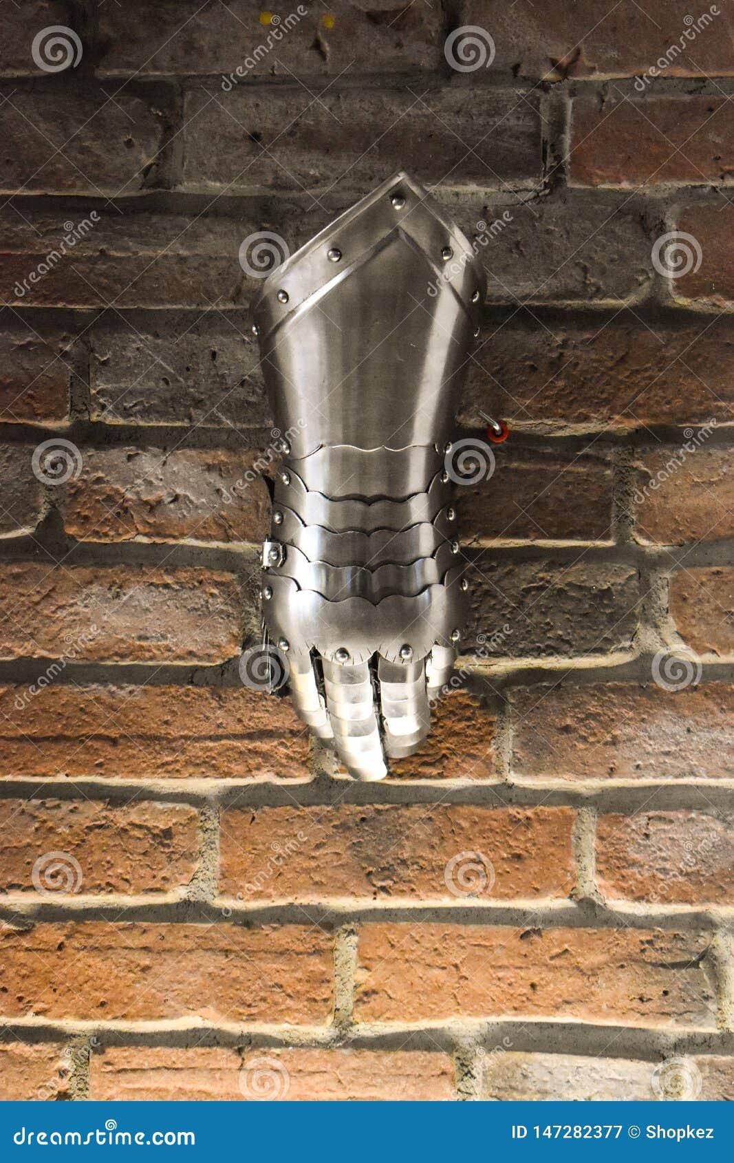 Luva de metal medieval, detalhe de pe?a da armadura antiga, detalhe de guerra Luva de brilho do ferro contra o fundo da parede de