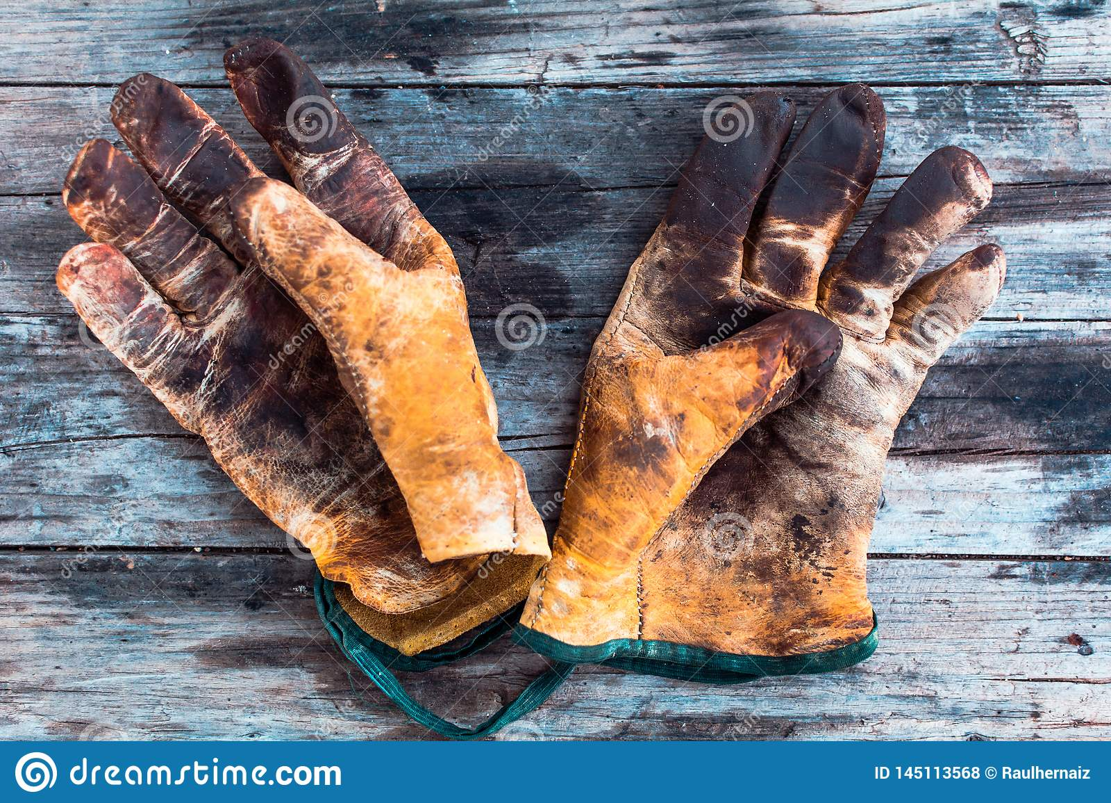 Luvas de trabalho velhas e sujas sobre a tabela de madeira, luvas para cada dedo