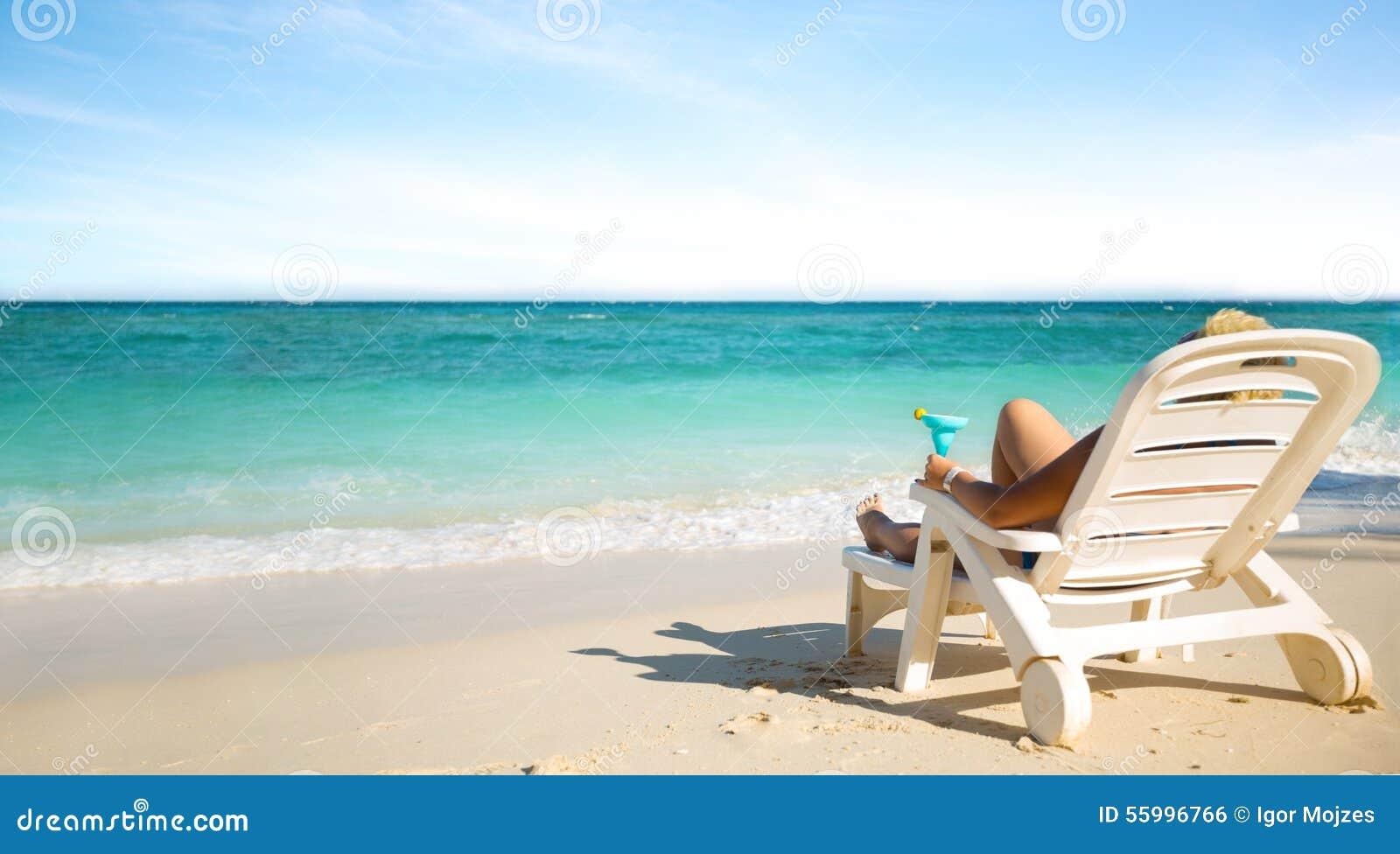 Luxe het vrouwelijke zonnebaden op het strand