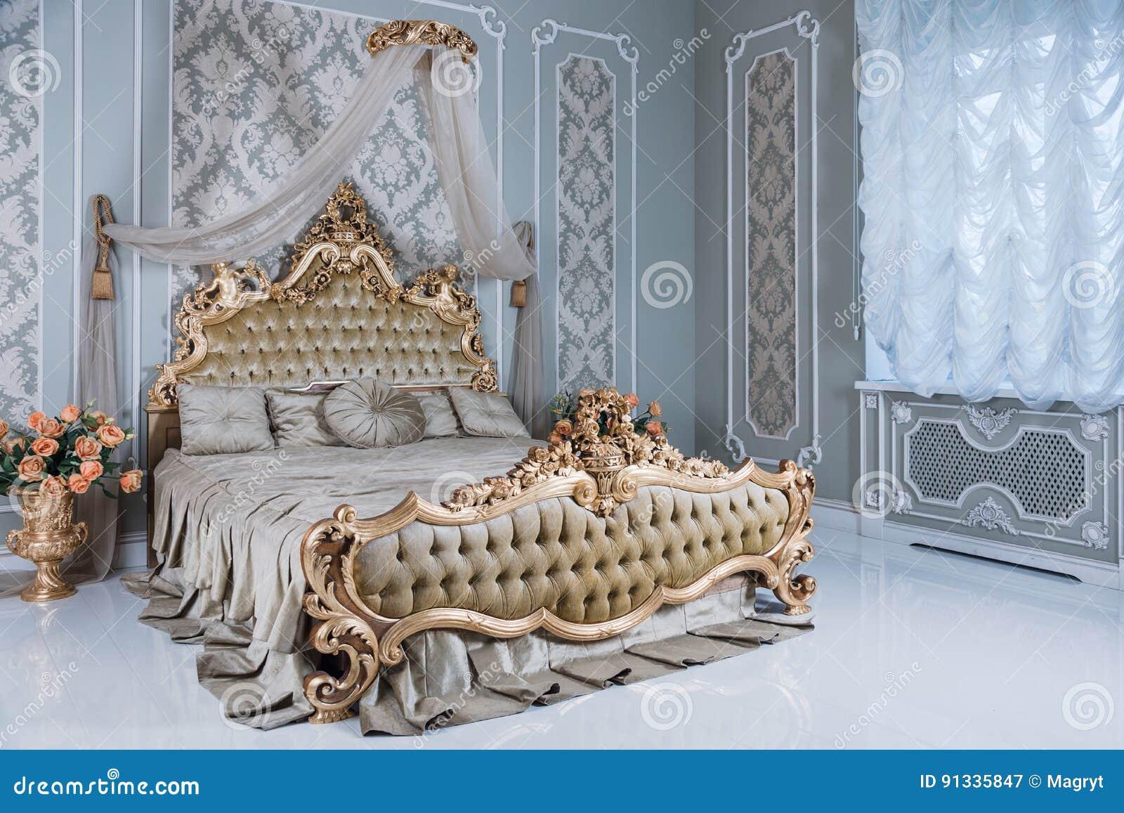 Luxeslaapkamer in lichte kleuren met gouden meubilairdetails Groot comfortabel dubbel koninklijk bed in elegante schrijver uit de