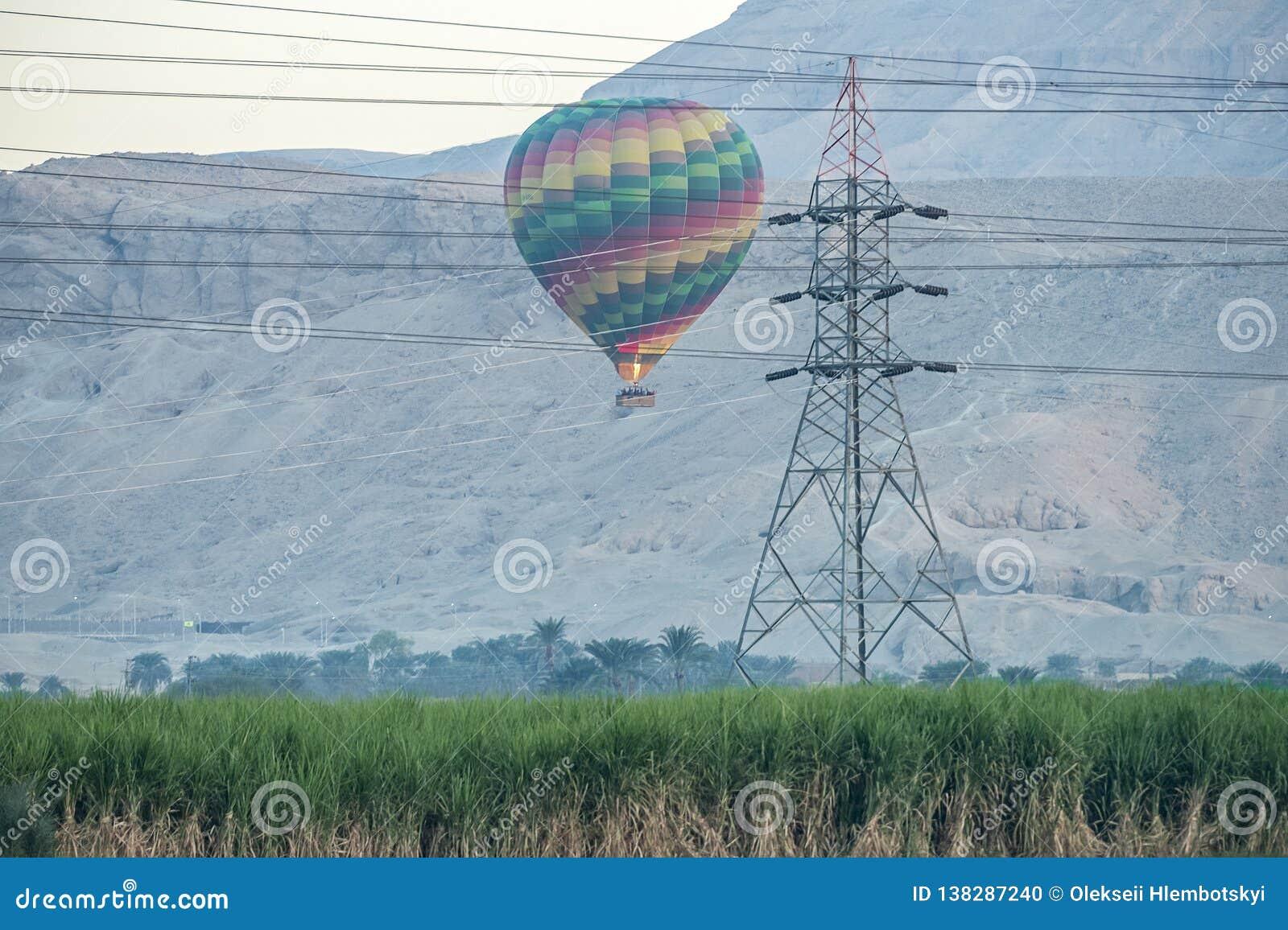 12/11/2018 Luxor, Egipt gorące powietrze balony wzrasta przy wschód słońca nad zieloną oazą w pustyni