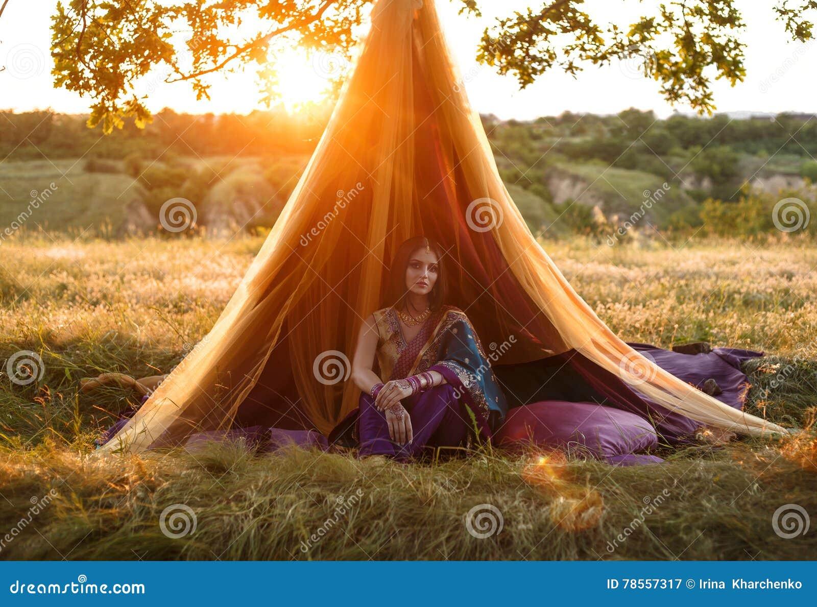 Luxuriöses indisches Mädchen sitzt in einem Zelt draußen, bei Sonnenuntergang