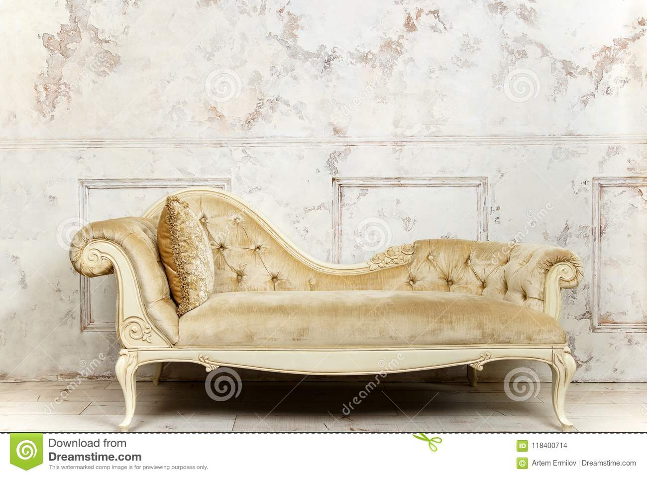 Luxurious Golden Sofa On A Background Of Old White Wall Stock Photo