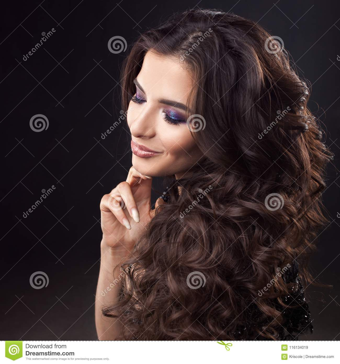 Luxurious hair. Portrait of a young attractive woman with gorgeous curly hair. Attractive brunette