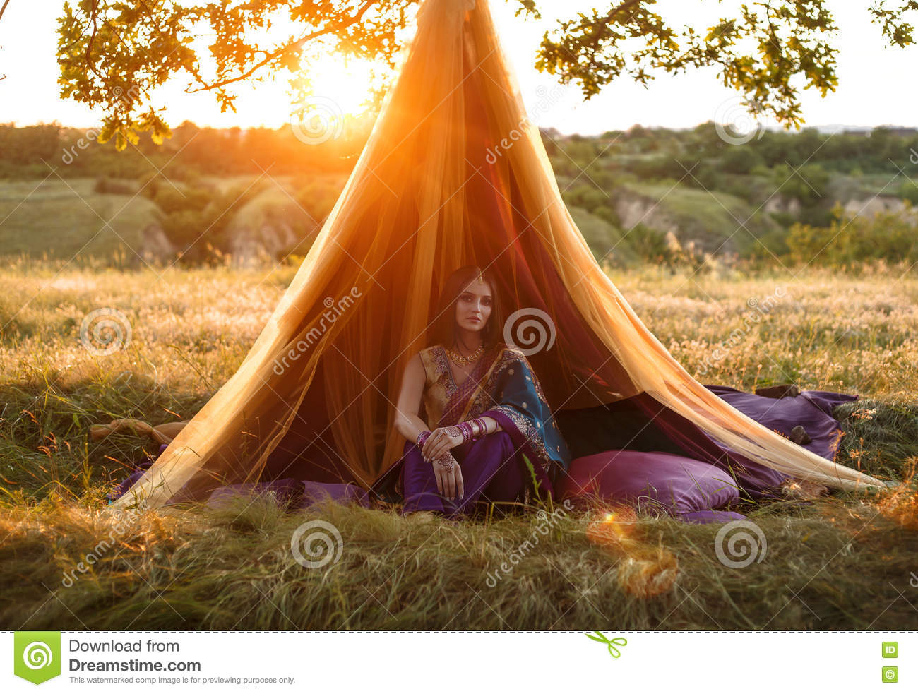 Luxurious Indian girl is sitting in a tent outdoors, at sunset.