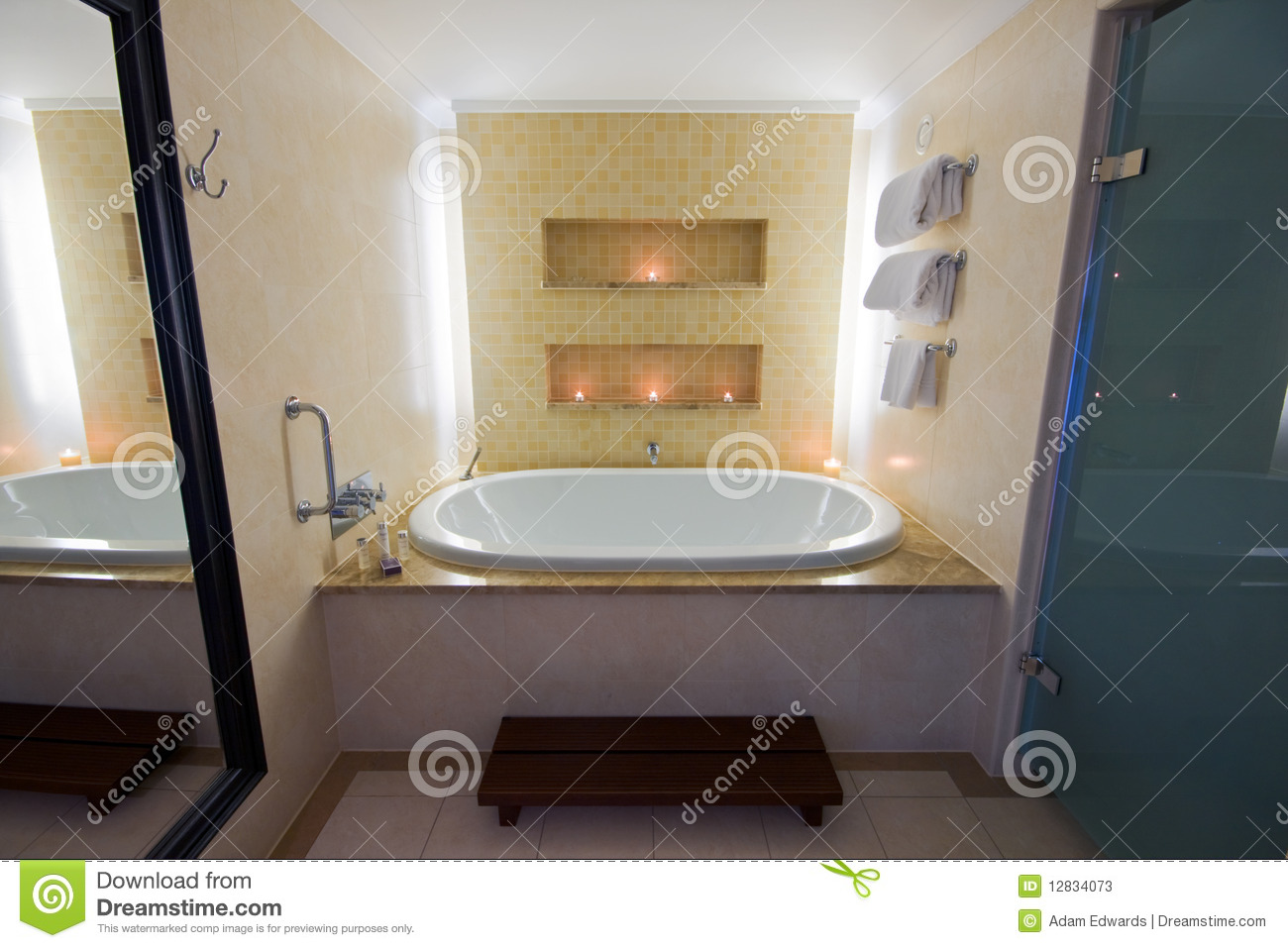 Luxury bathroom with large bath and lit candles stock for Large bathroom pictures