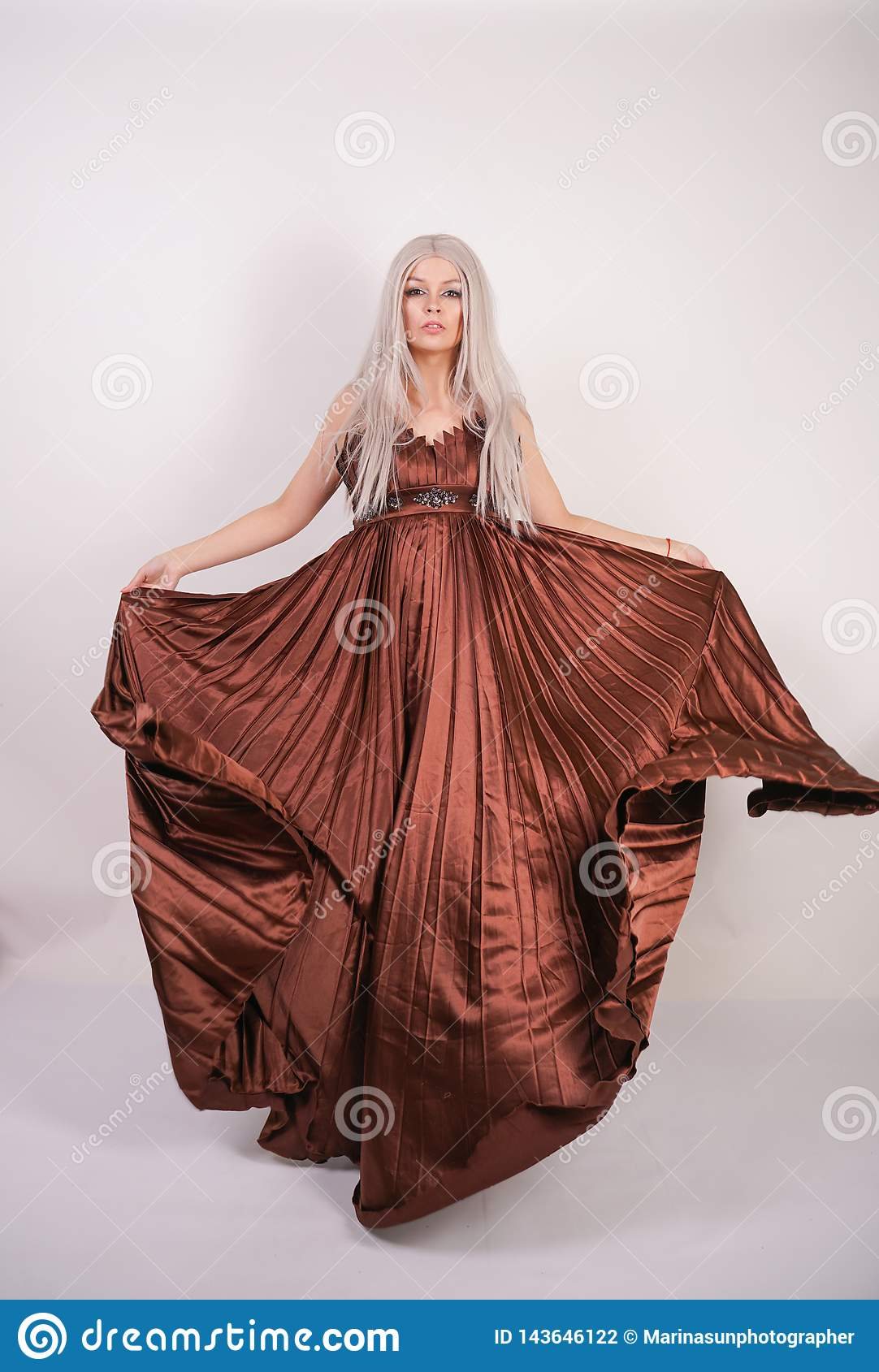 Luxury blonde caucasian model girl in chocolate color long evening dress made of pleated fabric waving a flying dress and stands o