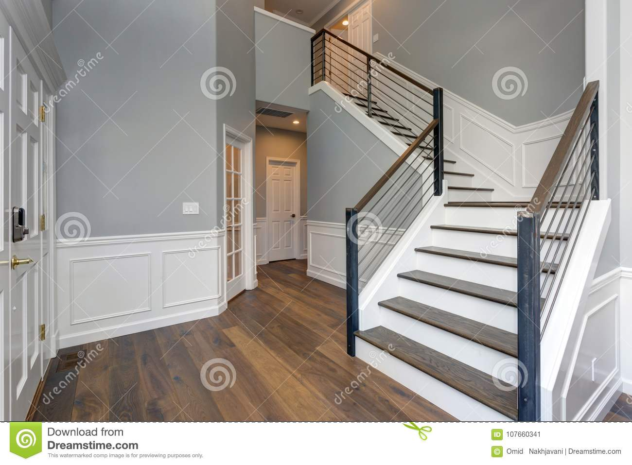 Stunning Two Story Entrance Foyer Design With White Wainscoting Grey Walls And A Staircase
