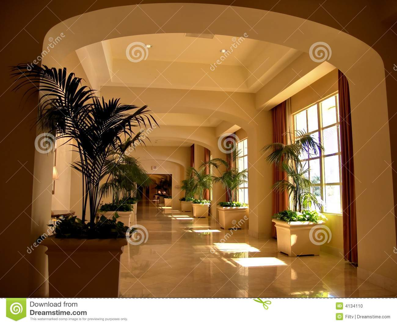 Luxuriously decorated hotel corridor. Warm lighting hall with marble ...