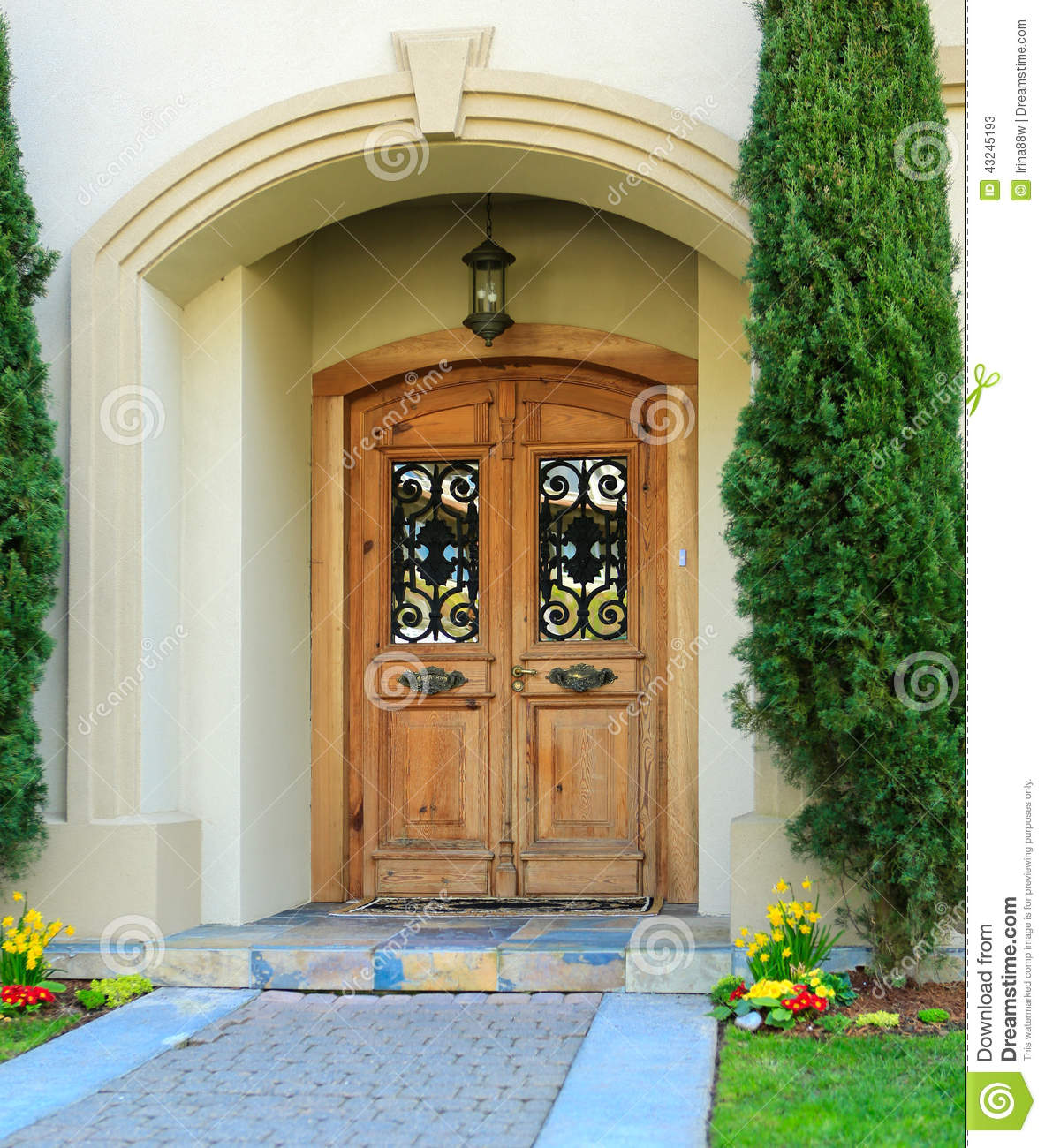 ... house entrance porch with wooden door and wrought iron details on it
