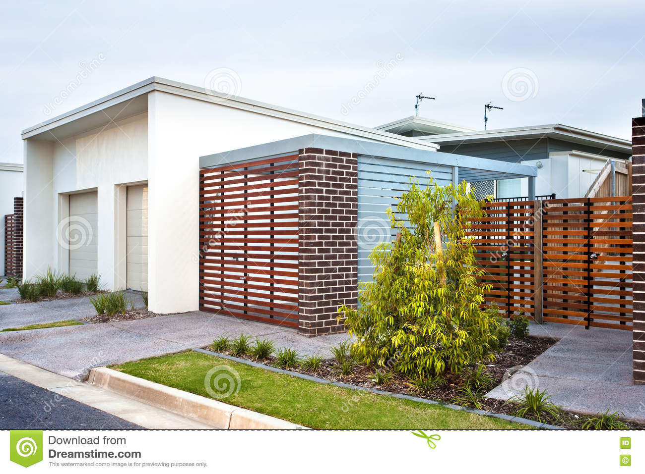 Luxury House Front Side With Wooden Gate And Garden Stock Photo