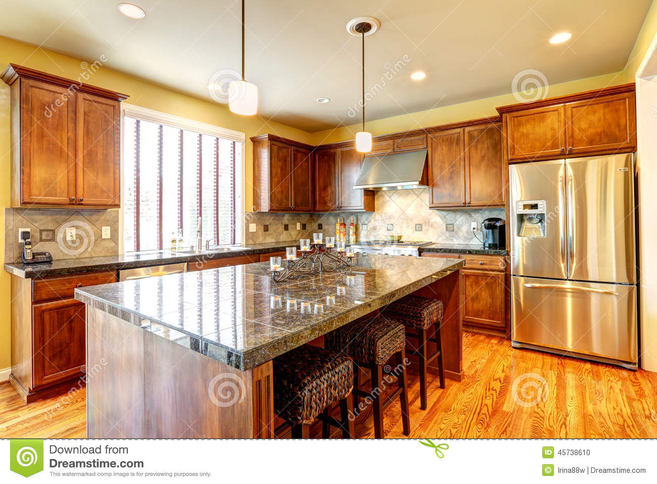 Spacious kitchen with stools at island in house stock for Kitchen remodeling companies