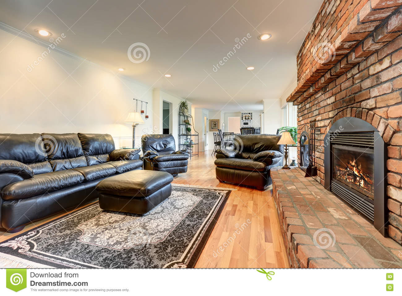 Luxury Living Room Interior With Black Leather Sofa Set And Brick Fireplace