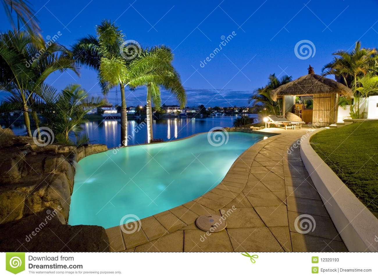 Luxury mansion outside deck with bali hut bar and pool dusk shot