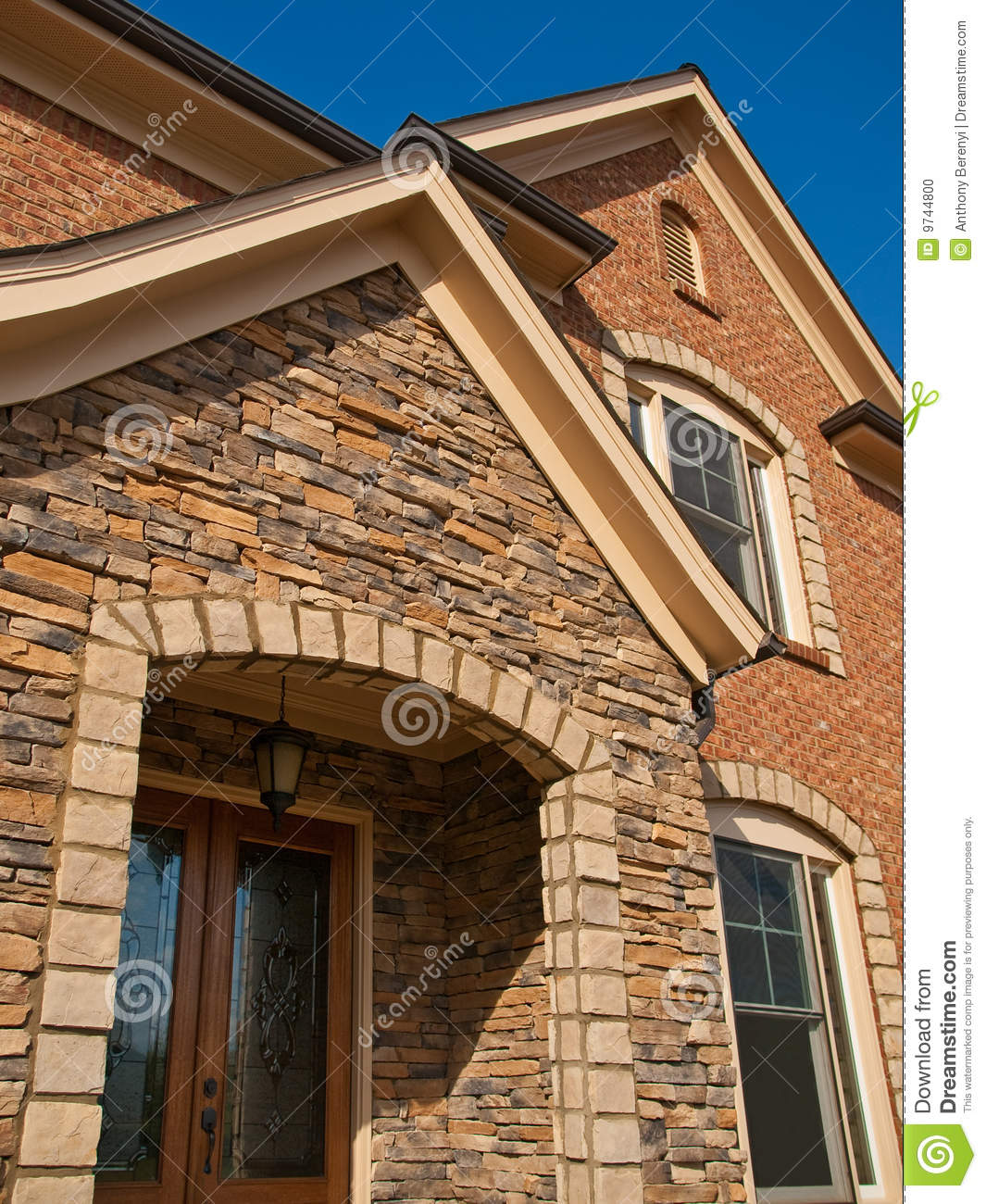 Luxury model home exterior stone arch entrance stock photo for Model home exterior photos