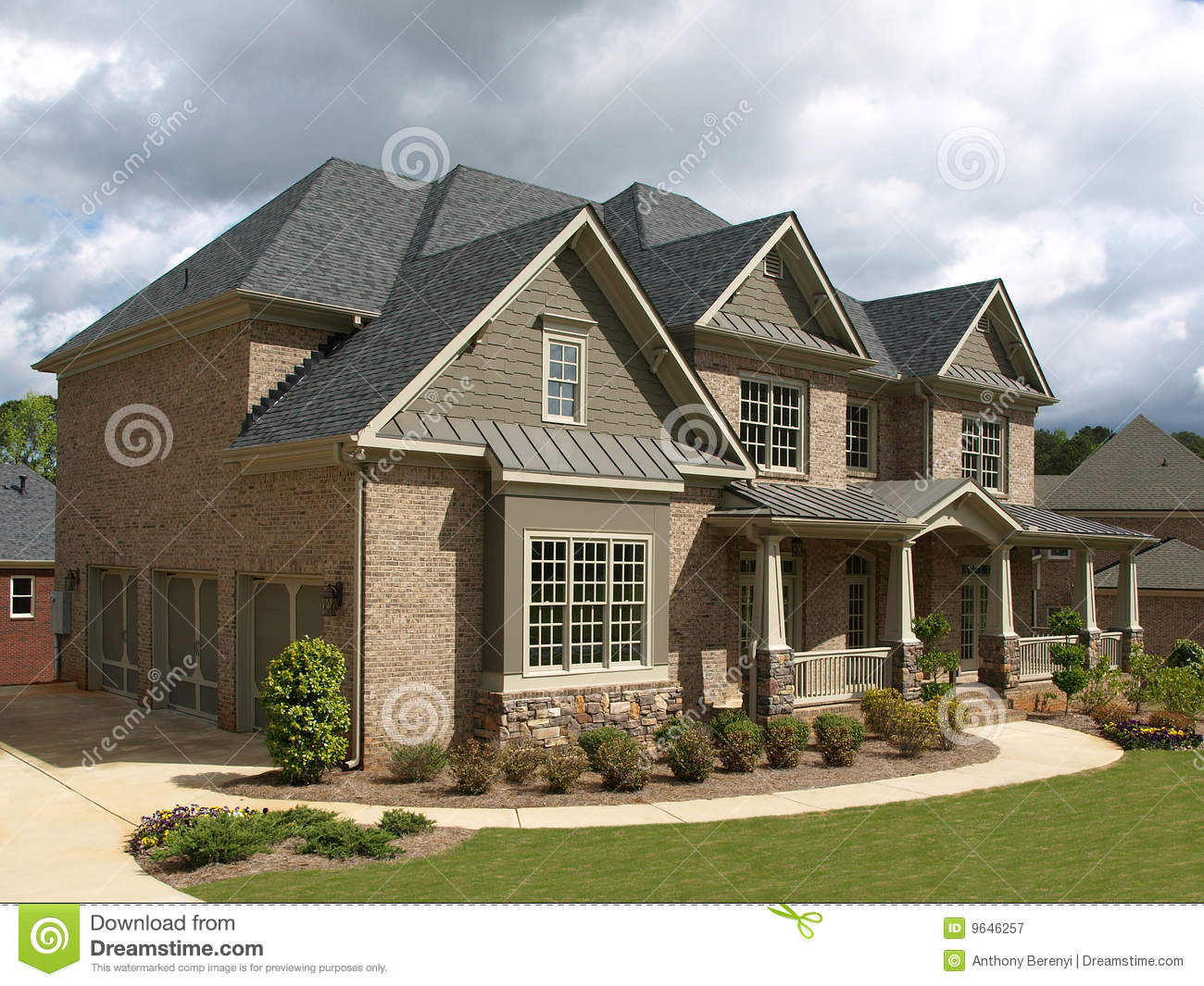 Home Exteriors: Luxury Model Home Exterior Stormy Weather Angle Stock