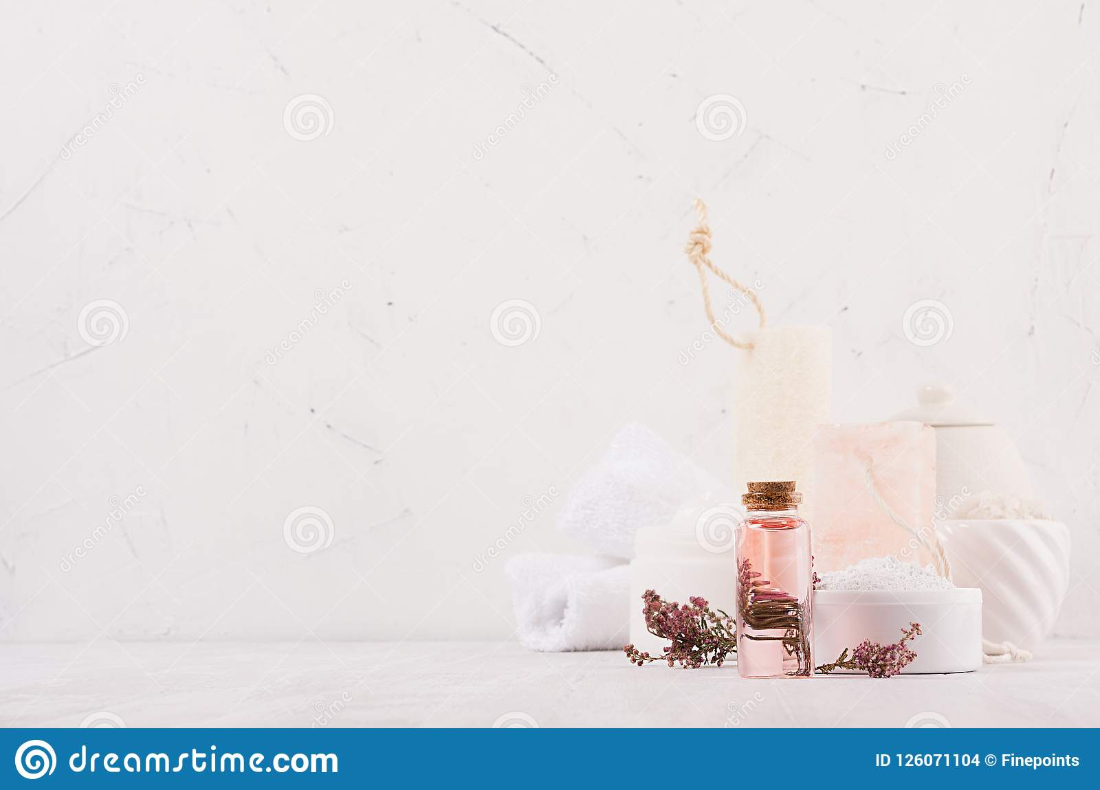 Luxury organic body and skin care spa cosmetics collection, pink oil, flowers, natural bath accessories on white wood background.