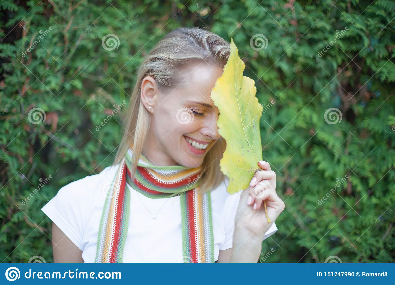 Luxury Portrait of a Beautiful young woman with natural makeup holds a big green leaf on a blurred green background. Spa and