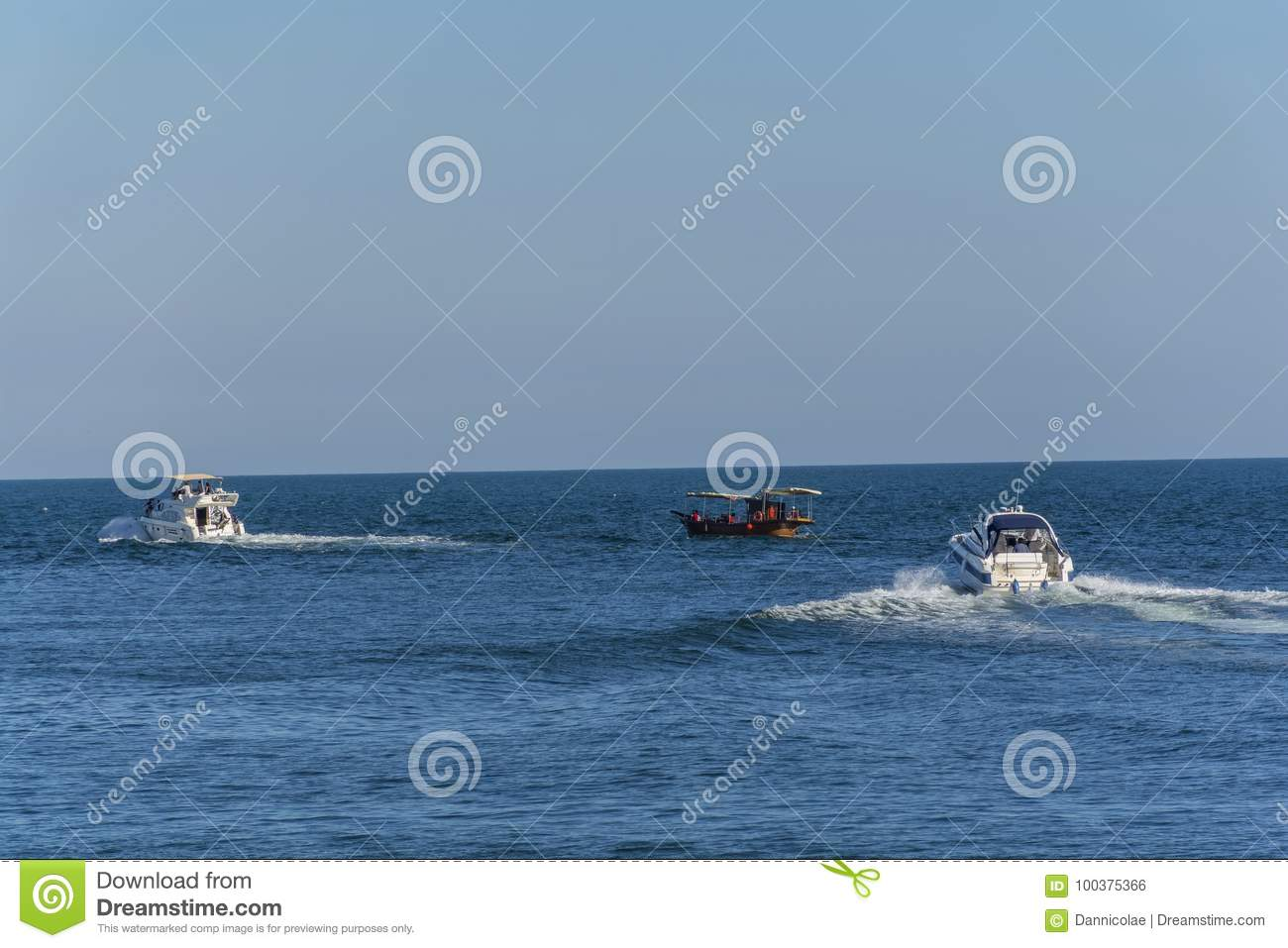Three Boats Moving Through The Blue Wather  Stock Photo