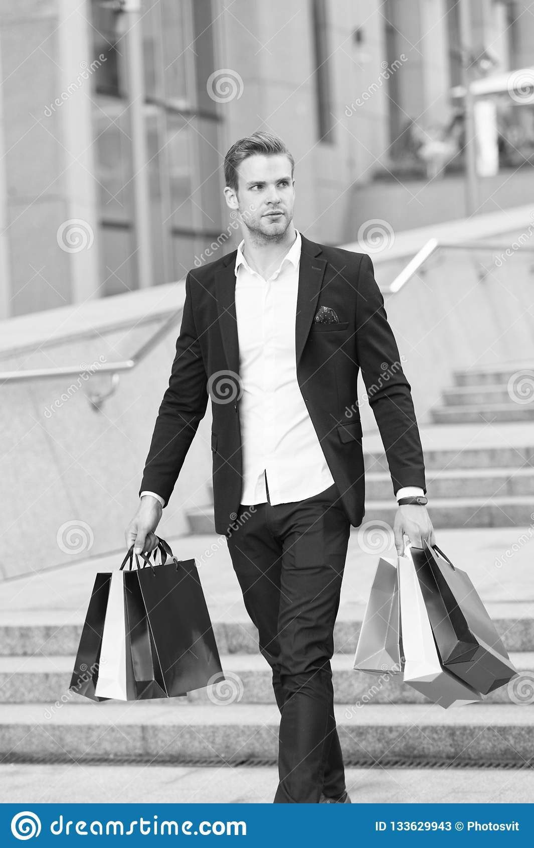 Luxury shopping. Boutique gallery client. Man shopper carries shopping bags urban background. Successful businessman