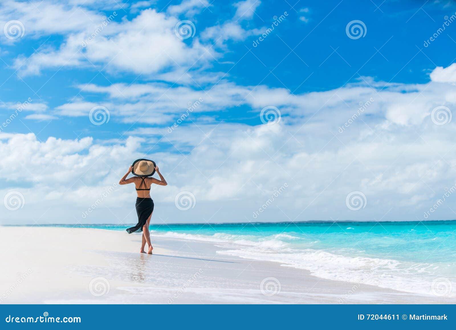 Luxury summer travel beach woman walking by ocean
