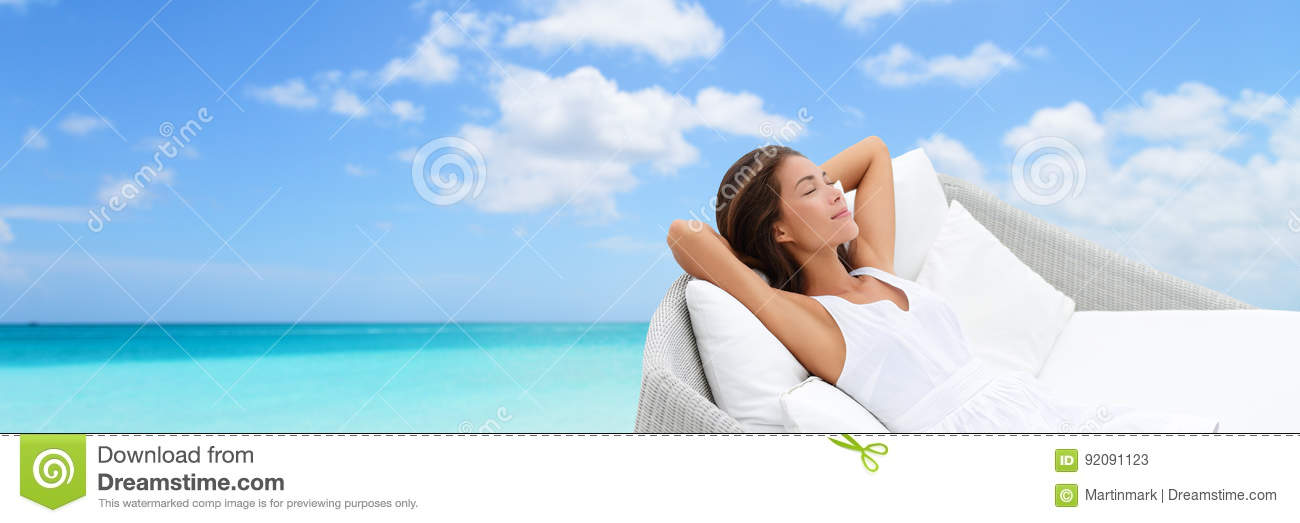 Luxury vacation woman relaxing on beach daybed