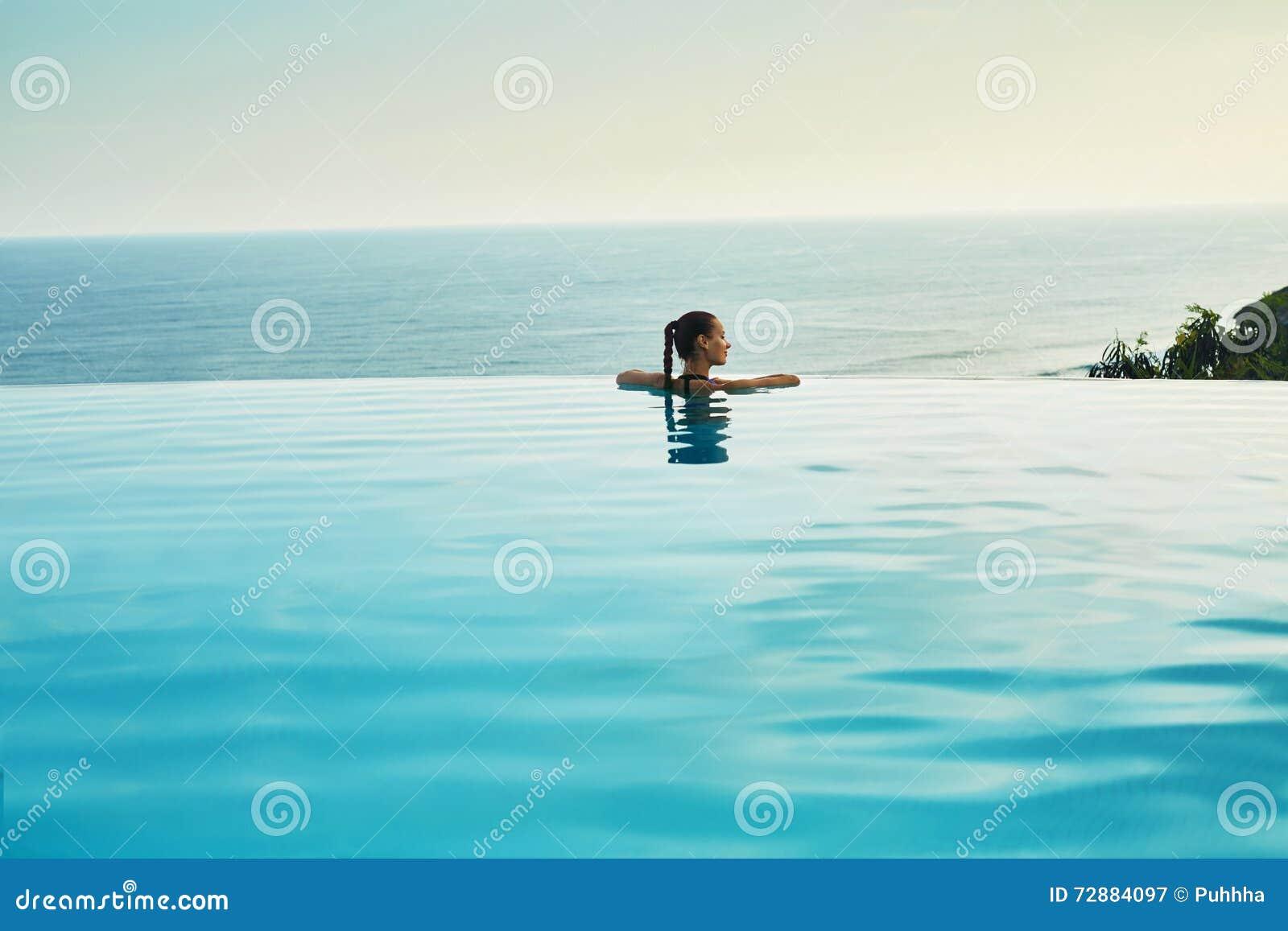 Luxus-Resort Frau, die im Pool sich entspannt Sommer-Reise-Ferien