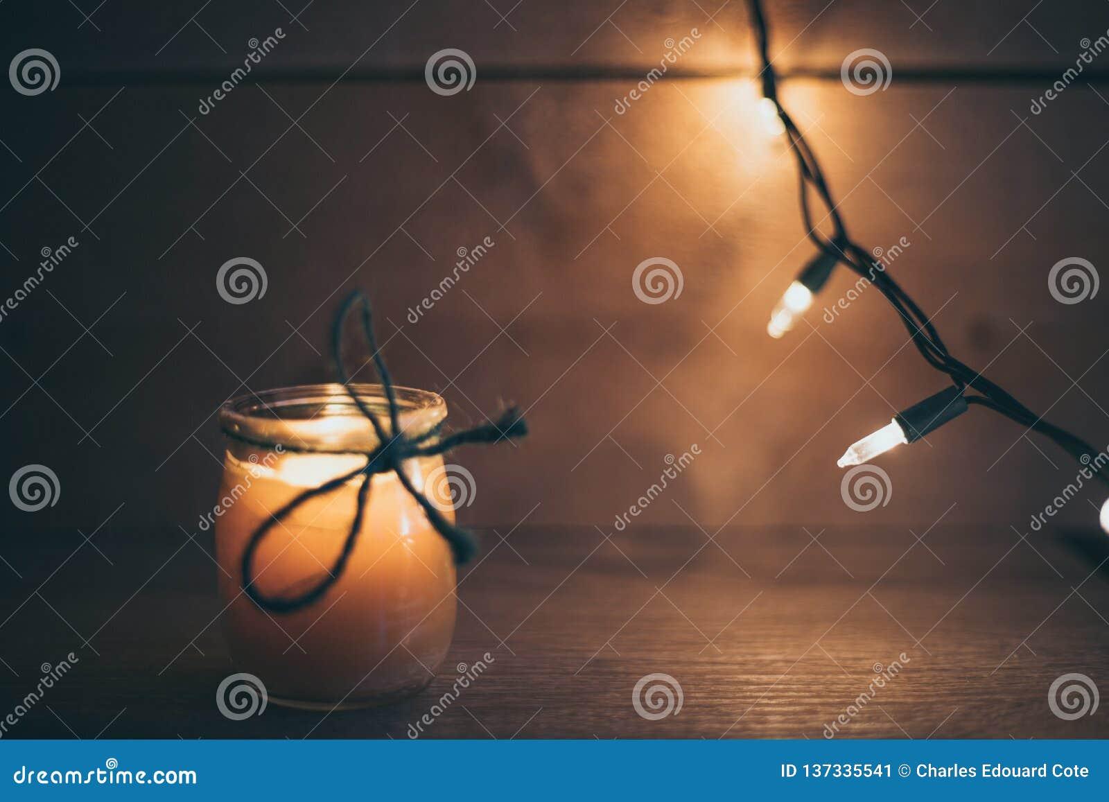 Luz anaranjada del fondo de madera con la vela