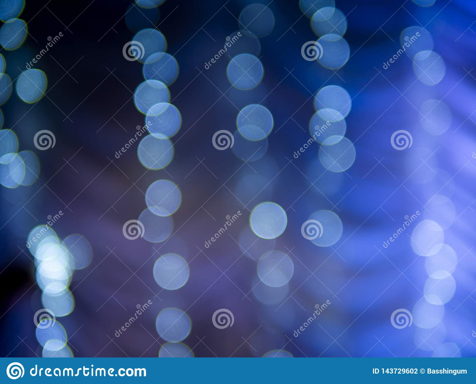 Luz branca abstrata do bokeh em escuro - fundo azul
