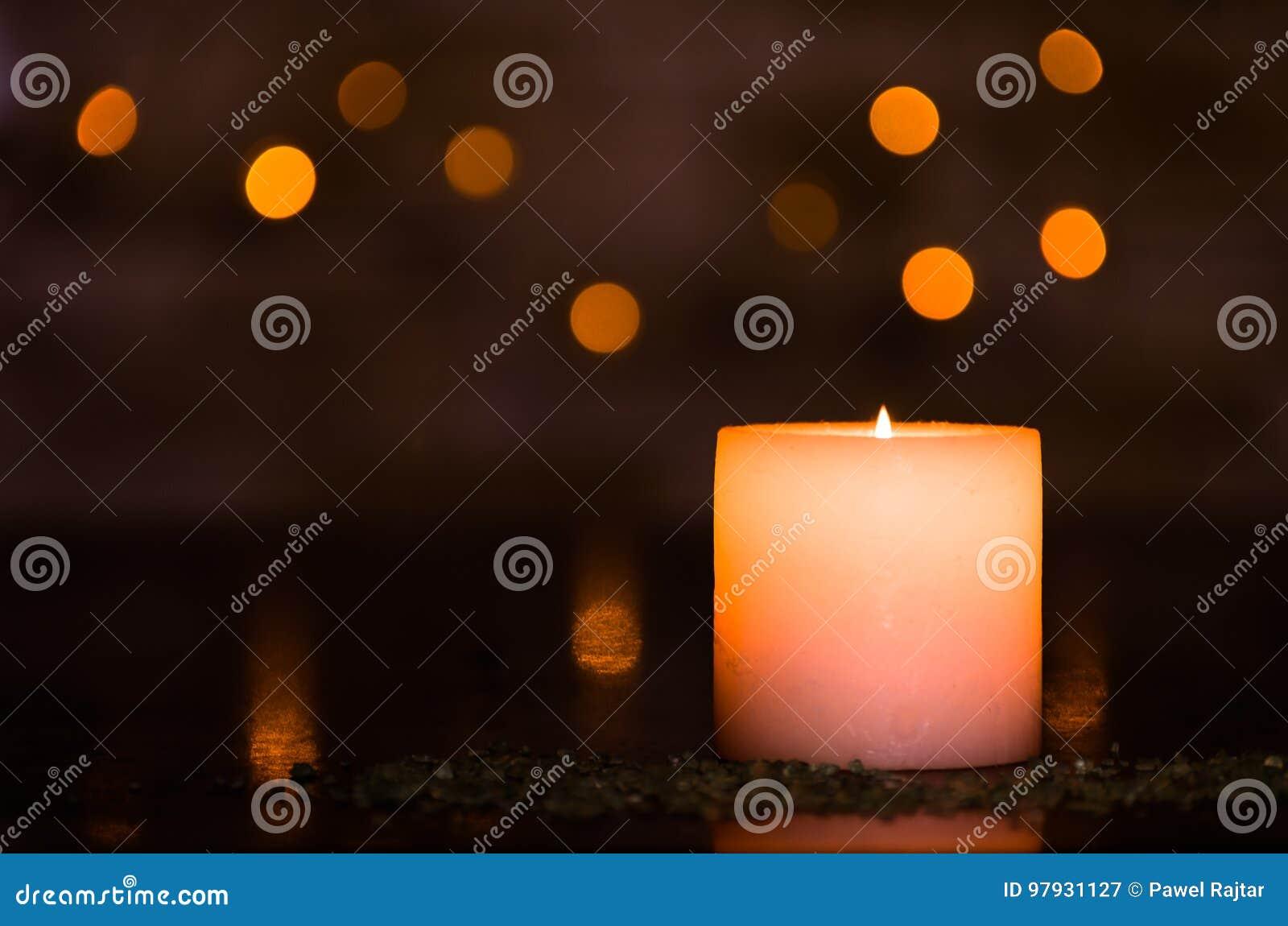 Luz de una vela cambiante con un bokeh ligero borroso agradable Perfeccione para el balneario