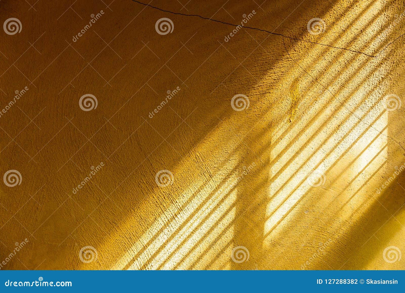 Luz del sol conmovedora de la tarde de la pared amarilla del cemento