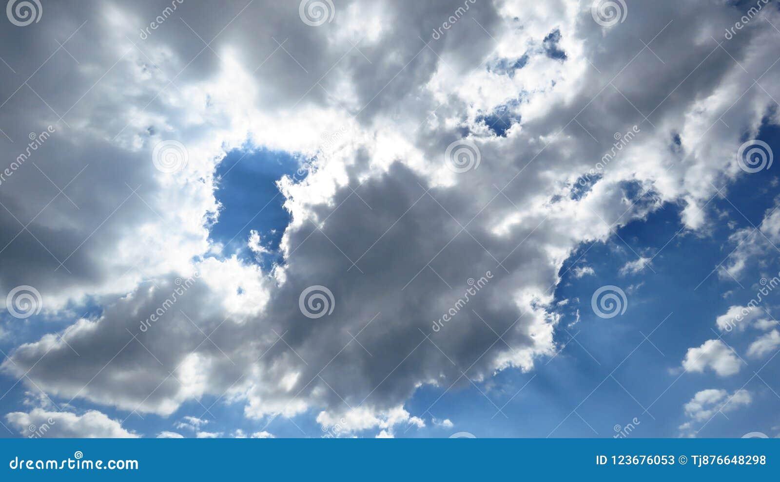 Luz del sol que viene a través de las nubes blancas y grises de la tormenta del claro, cielo azul
