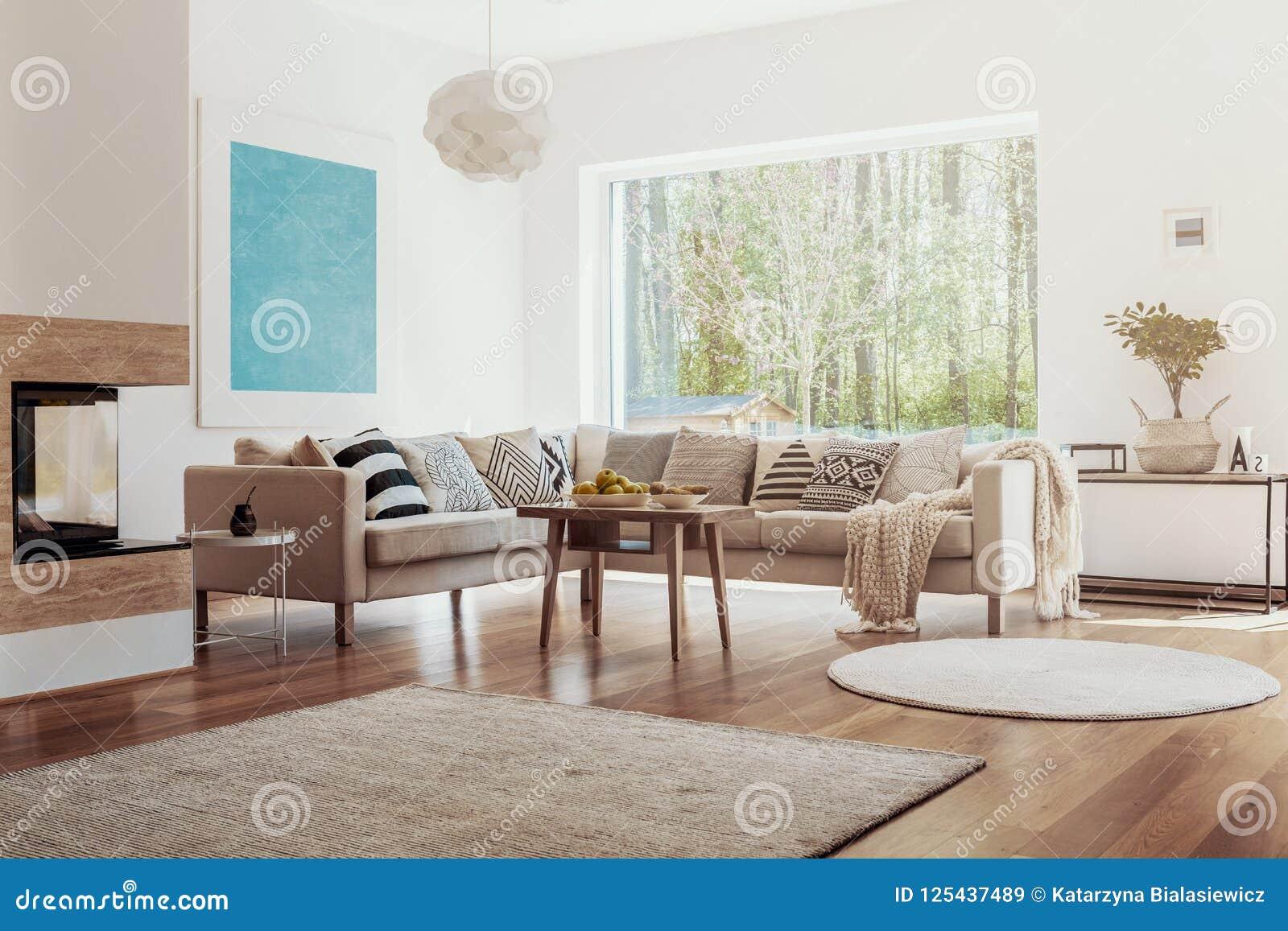 Luz del sol que viene a través de una ventana grande en un interior blanco y beige de la sala de estar con los cuencos de fruta e