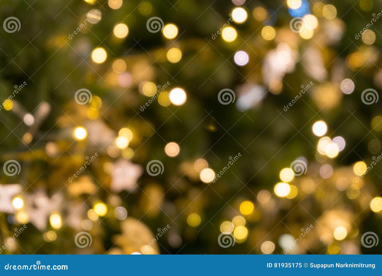 A luz do bokeh da árvore de Natal na cor dourada amarela verde, fundo abstrato do feriado, borra defocused