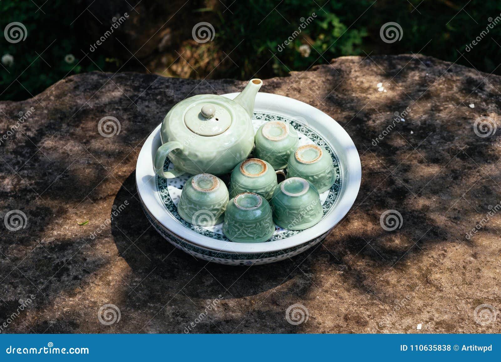 Luz - grupo de chá cerâmico verde que inclui o frasco, os copos e a placa na tabela de pedra sob a sombra da árvore em Ham Rong M