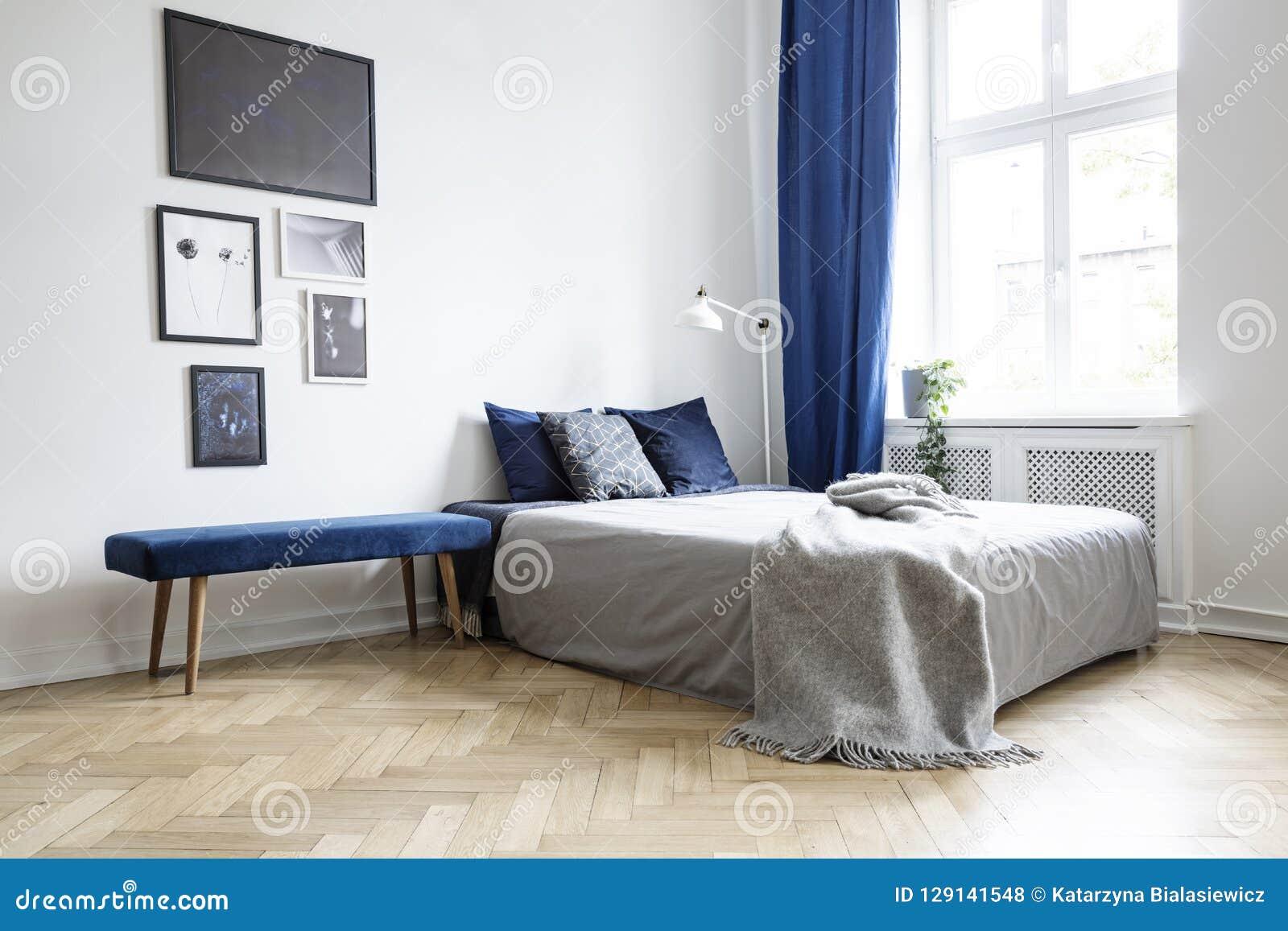 Luz natural que vem através de uma grande janela em um interior do quarto do branco e dos azuis marinhos com cama acolhedor e o a